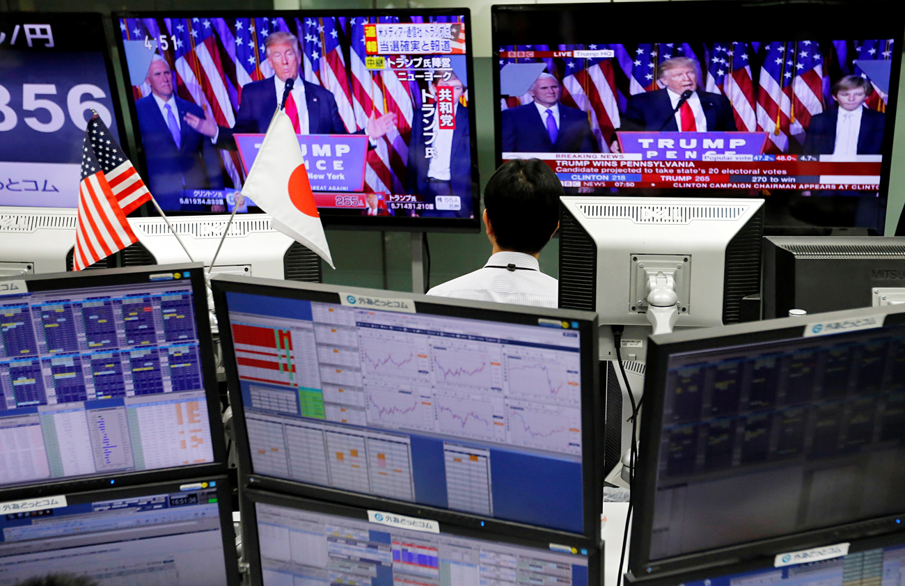 An employee of a foreign exchange trading company looks at monitors showing U.S. President elect Donald Trump speaking on TV news in Tokyo, Japan, November 9, 2016.