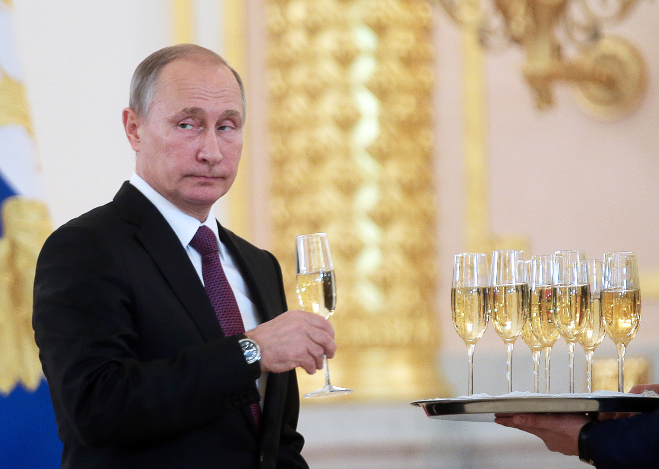 Russia's President Vladimir Putin holds a glass of champagne at a ceremony of presenting credentials by foreign ambassadors at the Alexander Hall of Moscow's Kremlin.