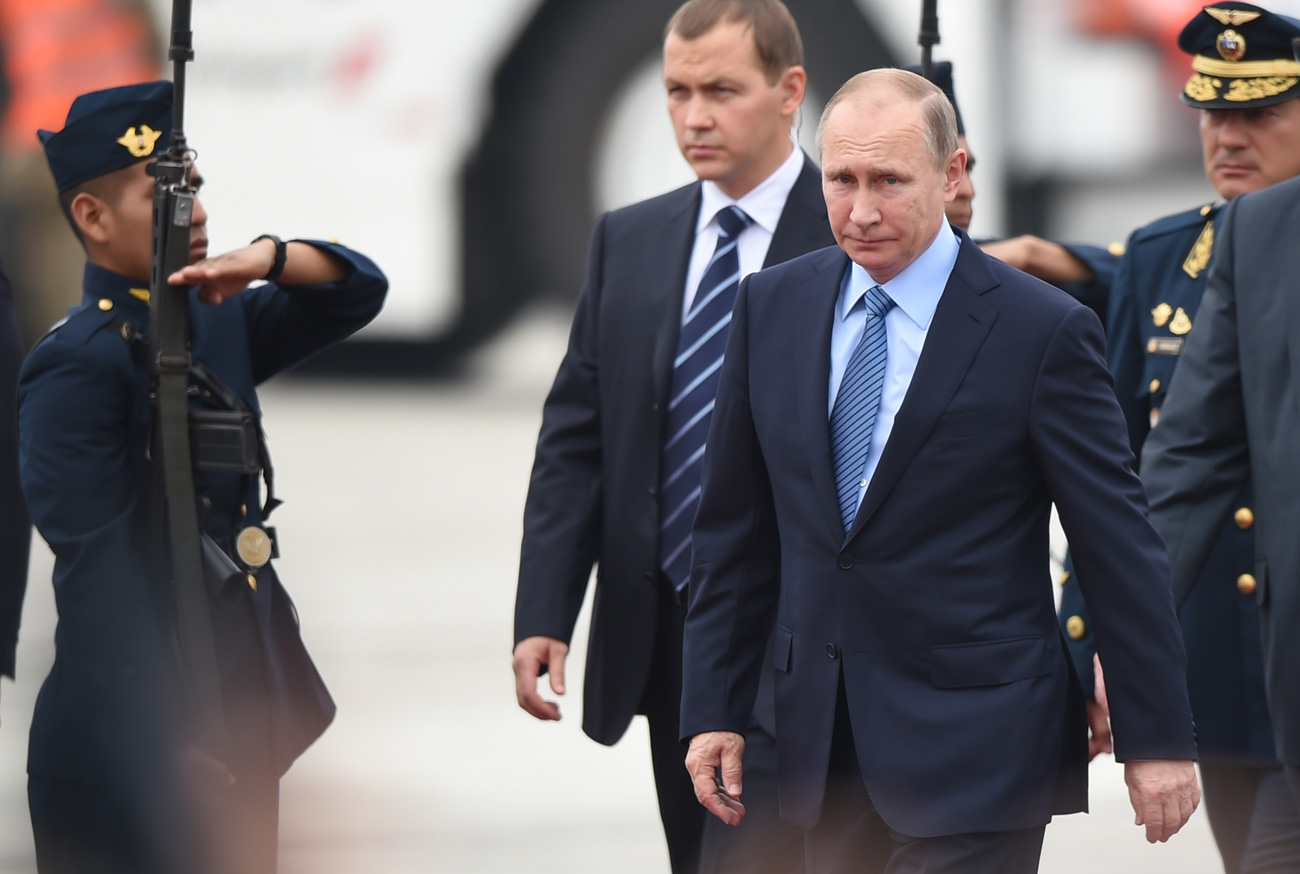 Russia's President Vladimir Putin walks upon arrival at Jorge Chavez International Airport in Lima to attend the Asia-Pacific Economic Cooperation (APEC) Summit on November 19, 2016. The summit of top world leaders was urged to defend free trade from rising protectionism after Donald Trump's election victory stoked fears that years of tearing down barriers to global commerce could be reversed.
