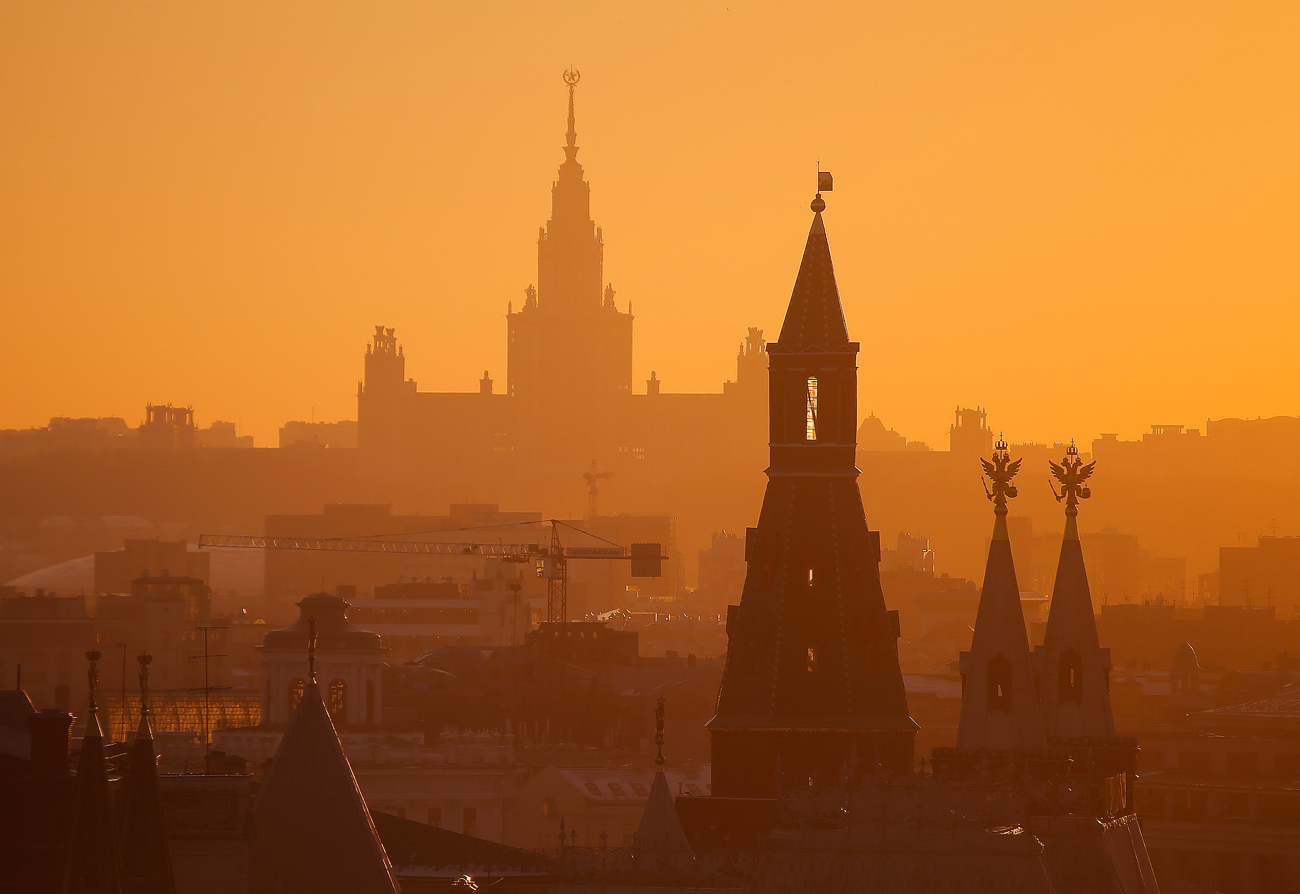 A view shows the main building of the Lomonosov Moscow State University (back) and a tower of the Kremlin (front) during sunset in Moscow, Russia