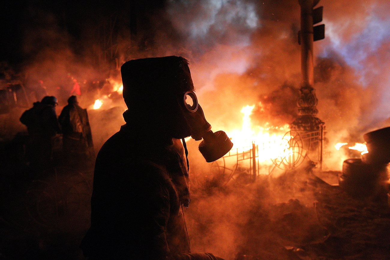 Anti-government protesters gather at a barricade at the site of clashes with riot police in Kiev.