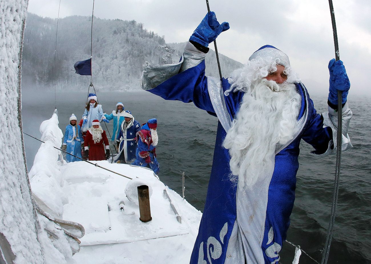"Members of the ""Skipper"" yacht club dressed as Ded Moroz, the Russian equivalent of Santa Claus, and his granddaughter Snegurochka (Snow Maiden) sail a yacht along the Yenisei River while marking the end of the sailboat season, with the air temperature at about minus 21 degrees Celsius (minus 5.8 degrees Fahrenheit), outside the Siberian city of Krasnoyarsk, Russia"