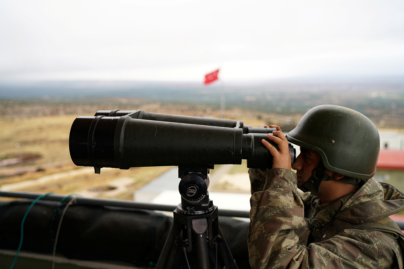 A Turkish soldier watches the border line between Turkey and Syria near the southeastern village of Besarslan, in Hatay province, Turkey.