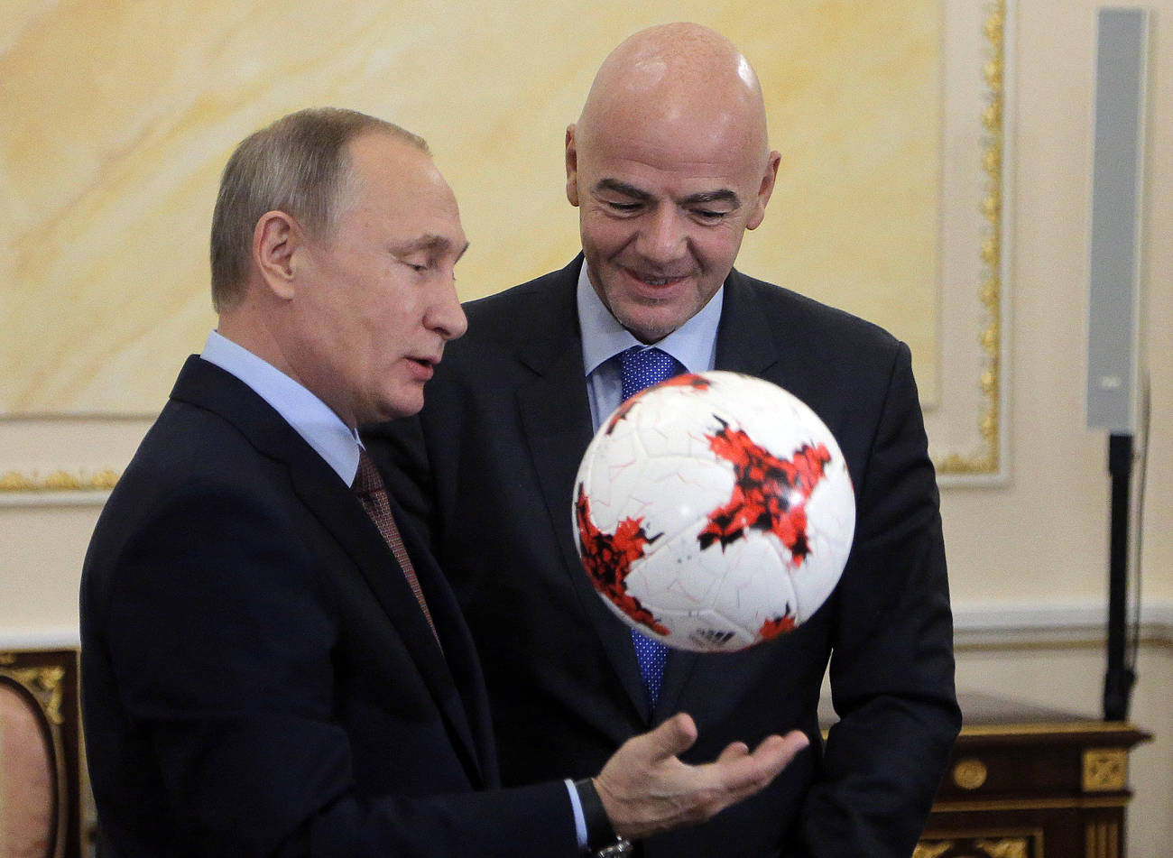 Russian President Vladimir Putin (L) receives an official match ball for the 2017 FIFA Confederations Cup from FIFA President Gianni Infantino during a meeting at the Kremlin in Moscow, Russia