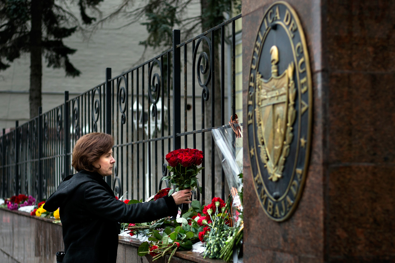 A woman lays a bunch of flowers to pay her last respect to Cuban President Fidel Castro, who has died on Friday, Nov. 25, 2016 at age 90 at the Cuban Embassy in Moscow, Russia, Saturday, Nov. 26, 2016. Russian President Vladimir Putin said in a condolences telegram to Raul Castro, that Fidel Castro was a sincere and reliable friend of Russia.