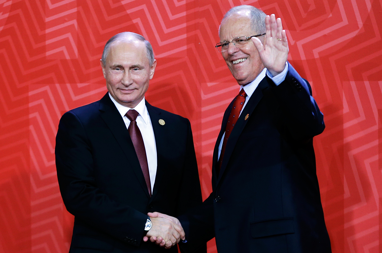Peru's President Pedro Kuczynski waves as he welcomes Russia's President Vladimir Putin to the opening session of the annual Asia Pacific Economic Cooperation, APEC, summit in Lima, Peru, Nov. 20, 2016.