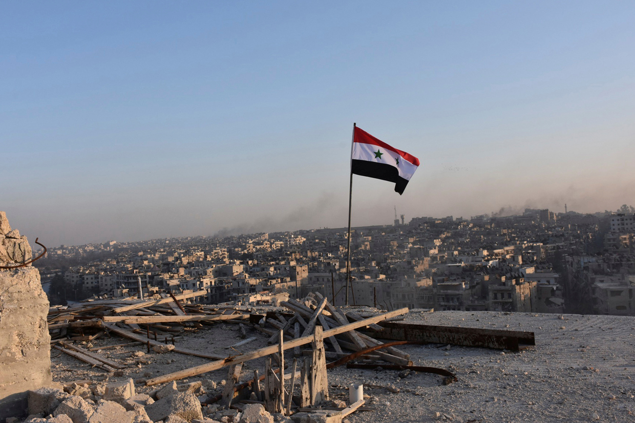 A Syrian national flag flutters near a general view of eastern Aleppo after Syrian government soldiers took control of al-Sakhour neigbourhood in Aleppo, Syria.