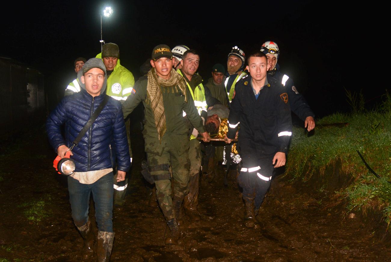 Funcionários do resgate carregam sobrevivente do acidente com time catarinense na Colômbia nesta madrugada.