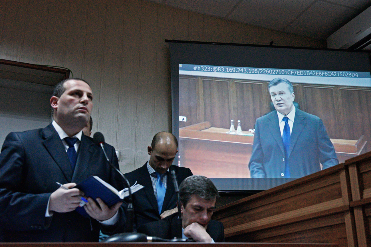 Former president of Ukraine Viktor Yanukovych, on the monitor, is seen here in Kiev's Svyatoshinsky Court as he testifies from Rostov Region Court via a video link on February 2014 unrest in Kiev.