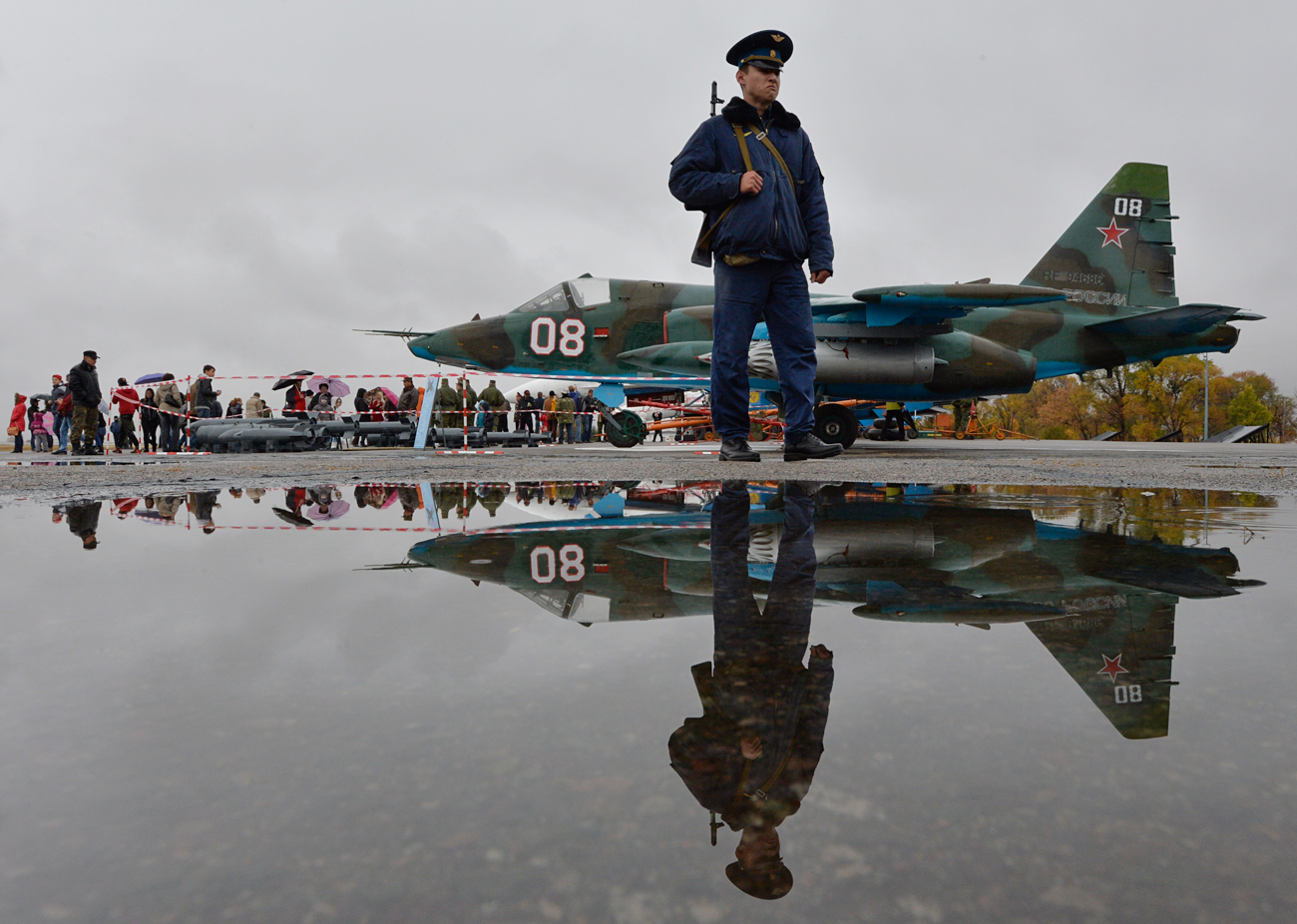 In this photo taken on Oct. 27, 2013, a Russian officer guard patrols at Kant, a Russian air base, outside Bishkek, Kyrgyzstan, with a Su-25 ground attack jet parked is in background.