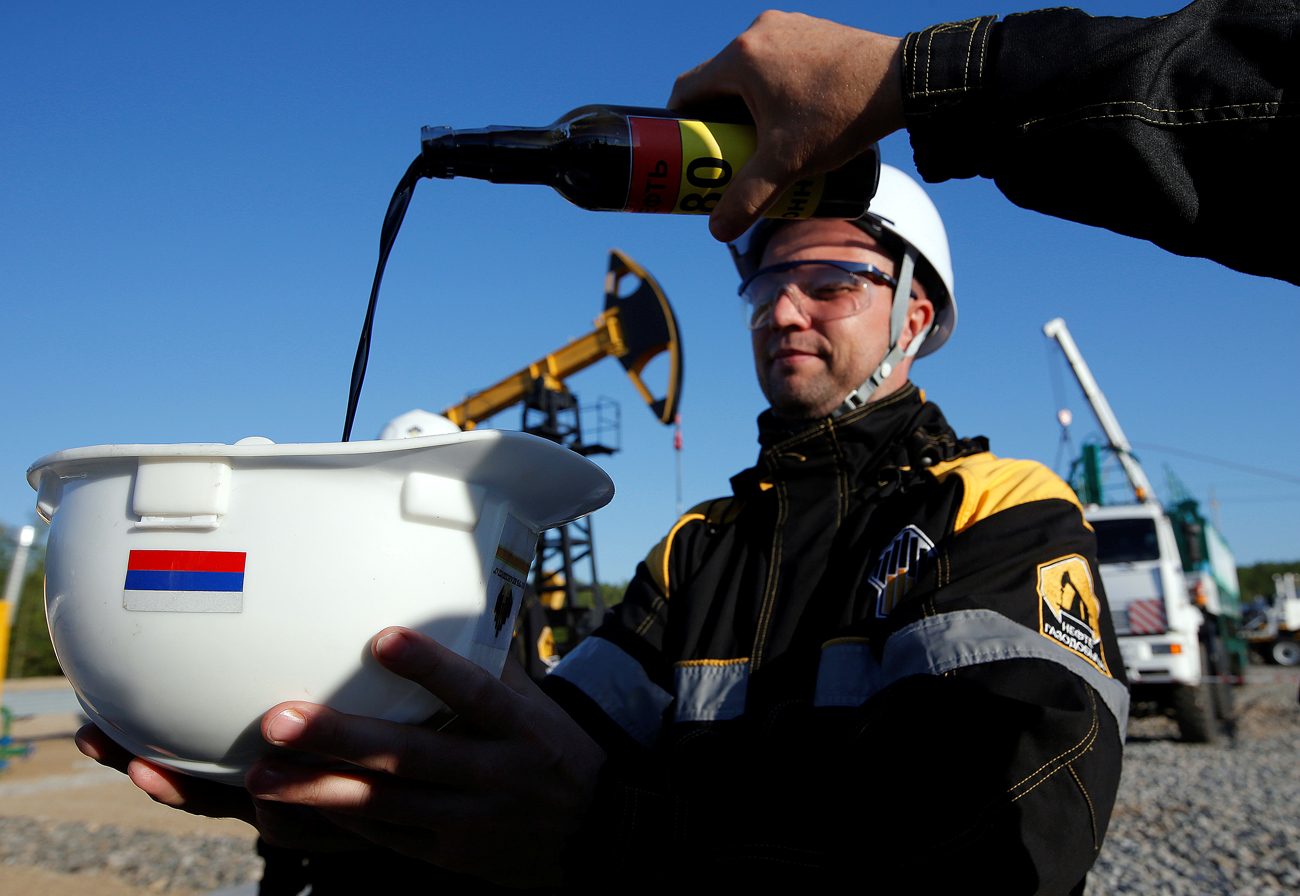 Employees demonstrate a sample of oil from a well at the central processing facility of the Rosneft-owned Priobskoye oil field outside the West Siberian city of Nefteyugansk.