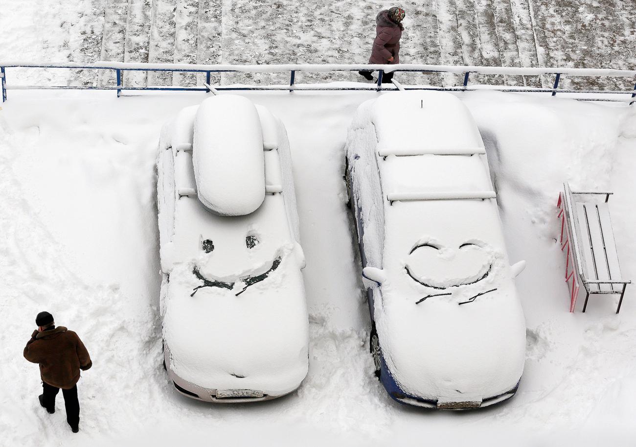 Паркирани авотомобили со насликано лице на нивните ветробрани по снежните врнежи во Краснојарск, Сибир, Русија.