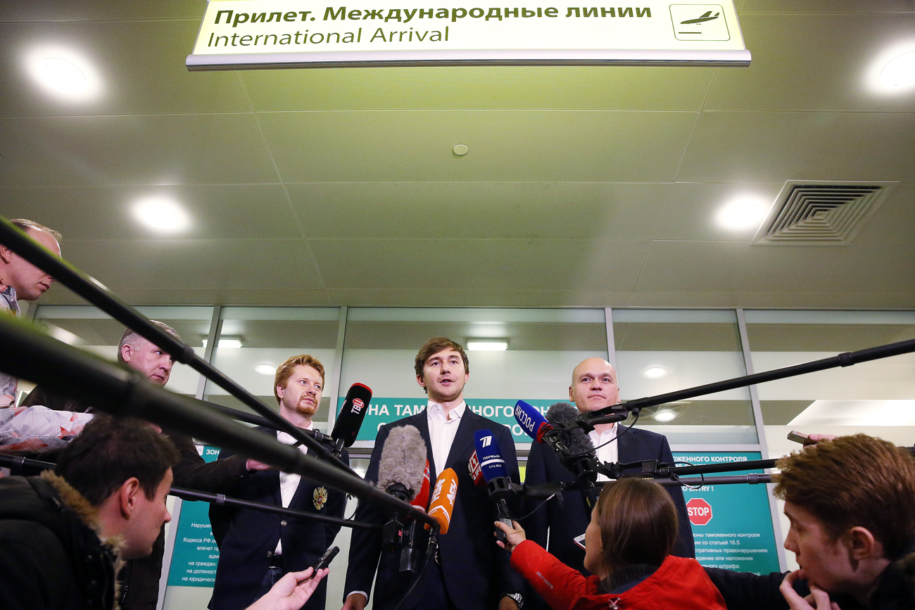 Russia's grandmaster Sergey Karjakin (C) and Russian Chess Federation president Andrei Filatov (R) talk to journalists as Sergey Karjakin arrives in Moscow.