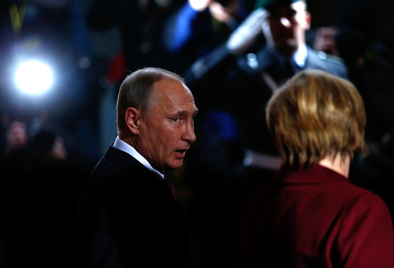 Russian President Vladimir Putin talks to German Chancellor Angela Merkel as he arrives for talks on a stalled peace plan for eastern Ukraine at the chancellery in Berlin, Germany.
