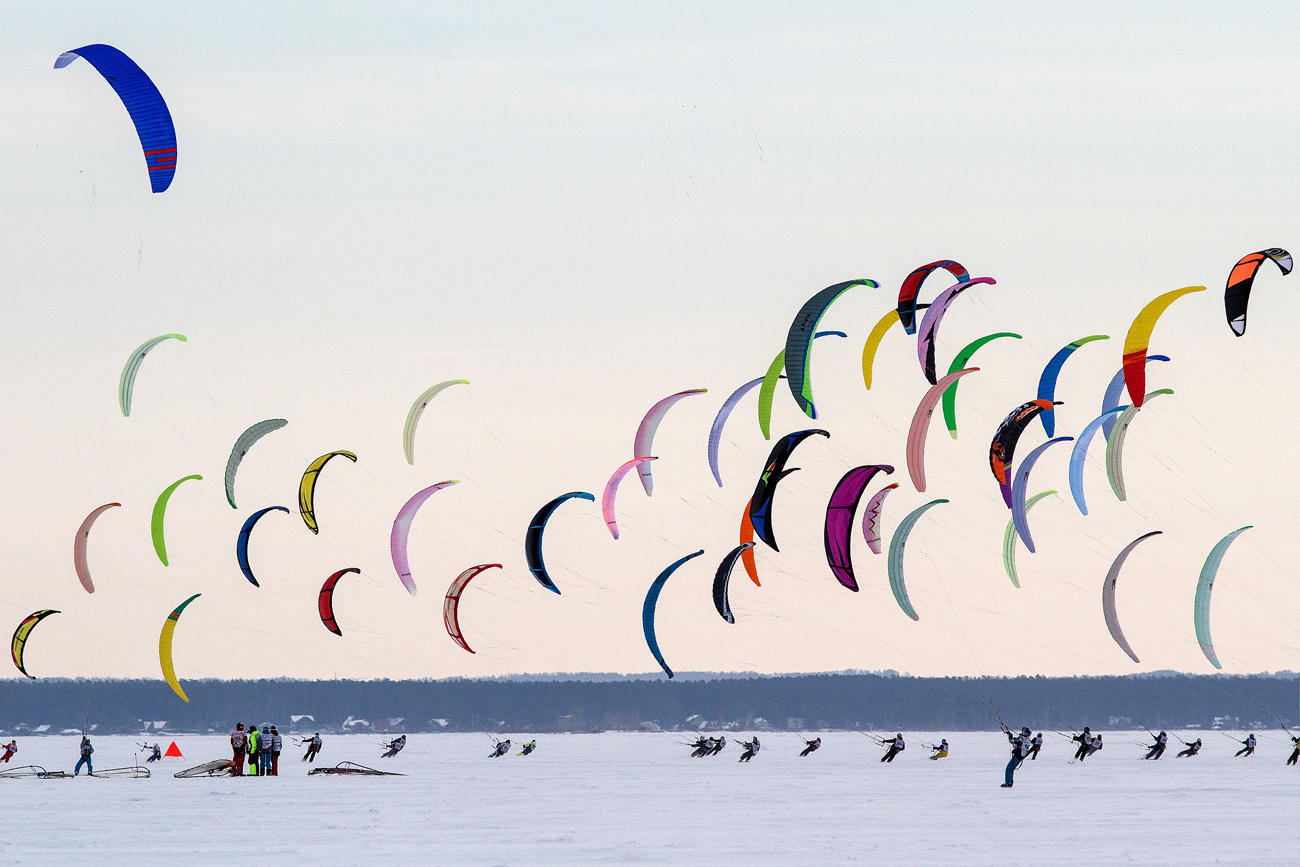 The participants of the Cup of Siberia in winter kiting - 2016 during the competition in the discipline of the course-flight on the ice reservoir of the Novosibirsk HPP