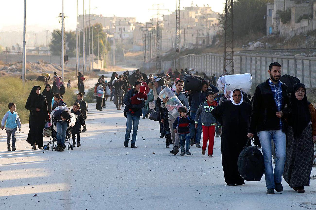 Un grupo de kurdos sirios sale de Alepo.