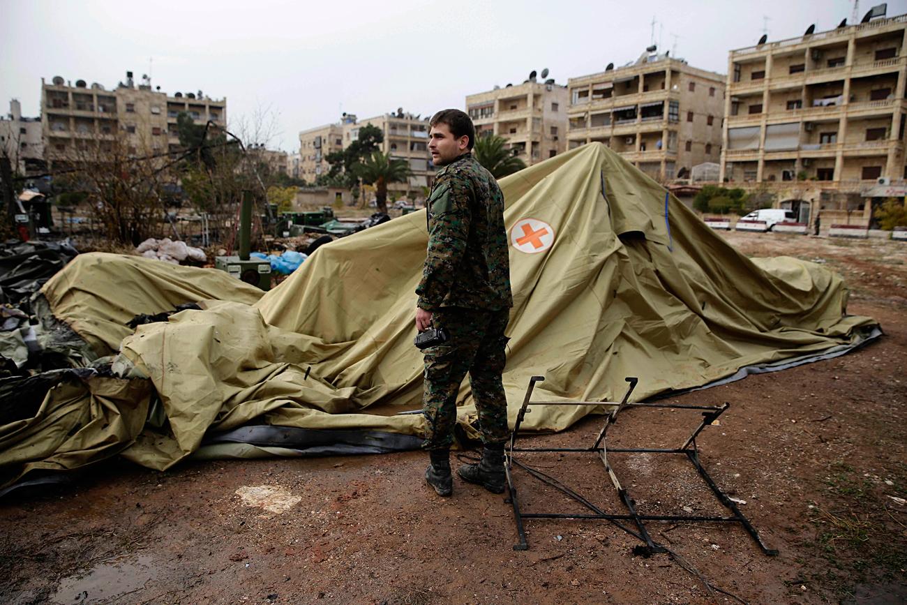 Seorang tentara Rusia menyambangi tenda medis yang terbakar akibat serangan pemberontak di Aleppo timur, Suriah, 5 Desember 2016.