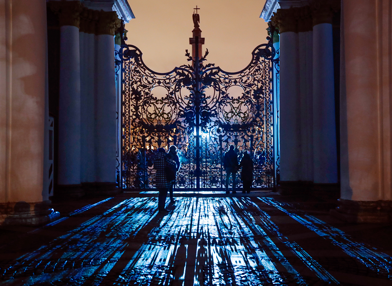 People look at illuminated Hermitage State Museum through the main gate during a light show marking the Day of Hermitage at the Dvortsovaya (Palace) square in St. Petersburg, Russia, Wednesday, Dec. 7, 2016.
