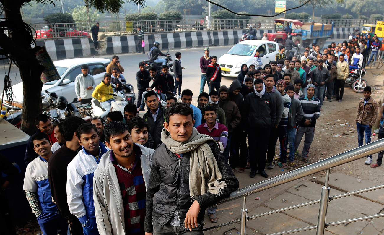 Indians wait outside a bank to withdraw money on the outskirts of New Delhi, India.