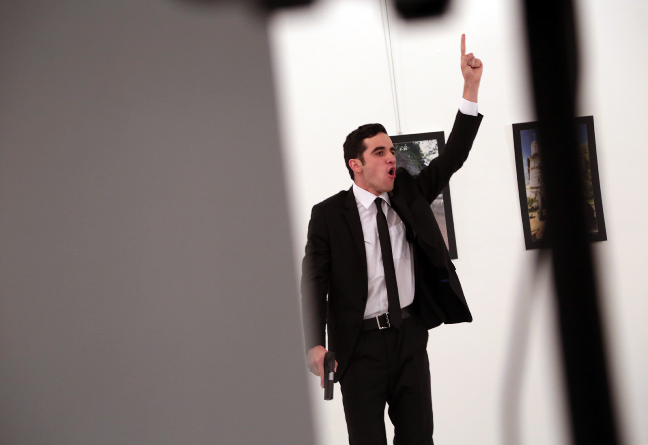 An unnamed gunman gestures after shooting the Russian Ambassador to Turkey, Andrei Karlov, at a photo gallery in Ankara, Turkey, Monday, Dec. 19, 2016. A gunman opened fire on Russia's ambassador to Turkey at a photo exhibition.