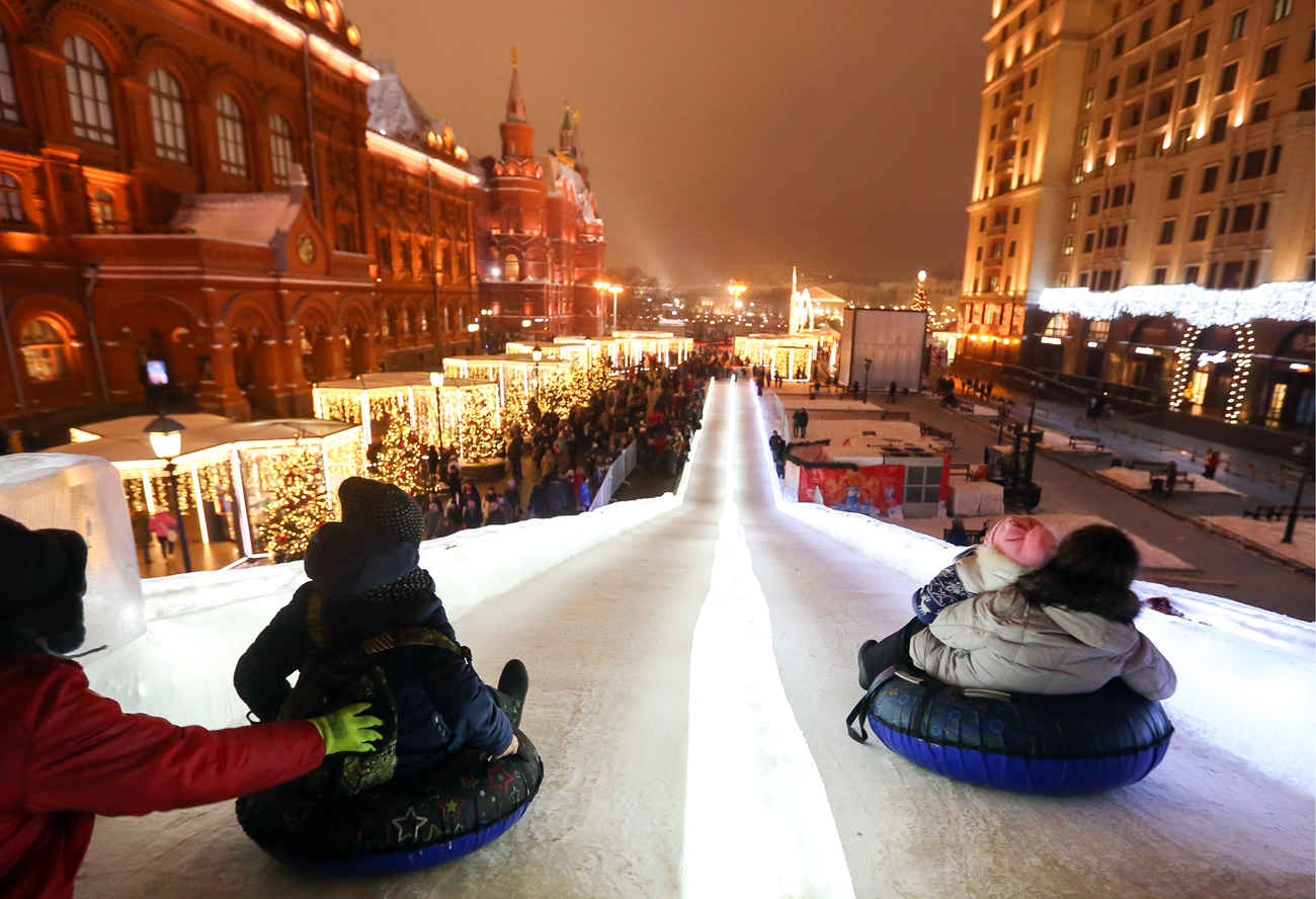 People slide down an icy slope on the Revolution Square in Moscow, Russia.