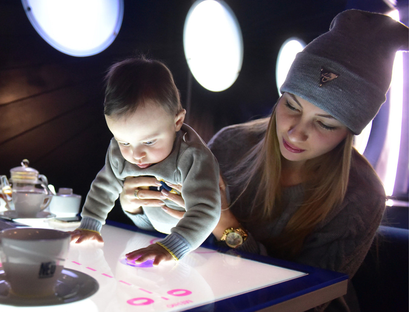 VLADIKAVKAZ, RUSSIA  A woman and a baby at the NEO interactive restaurant. The restaurant is equipped with interactive tables where people can view a list of dish ingredients, place an order or play games while waiting for meal.