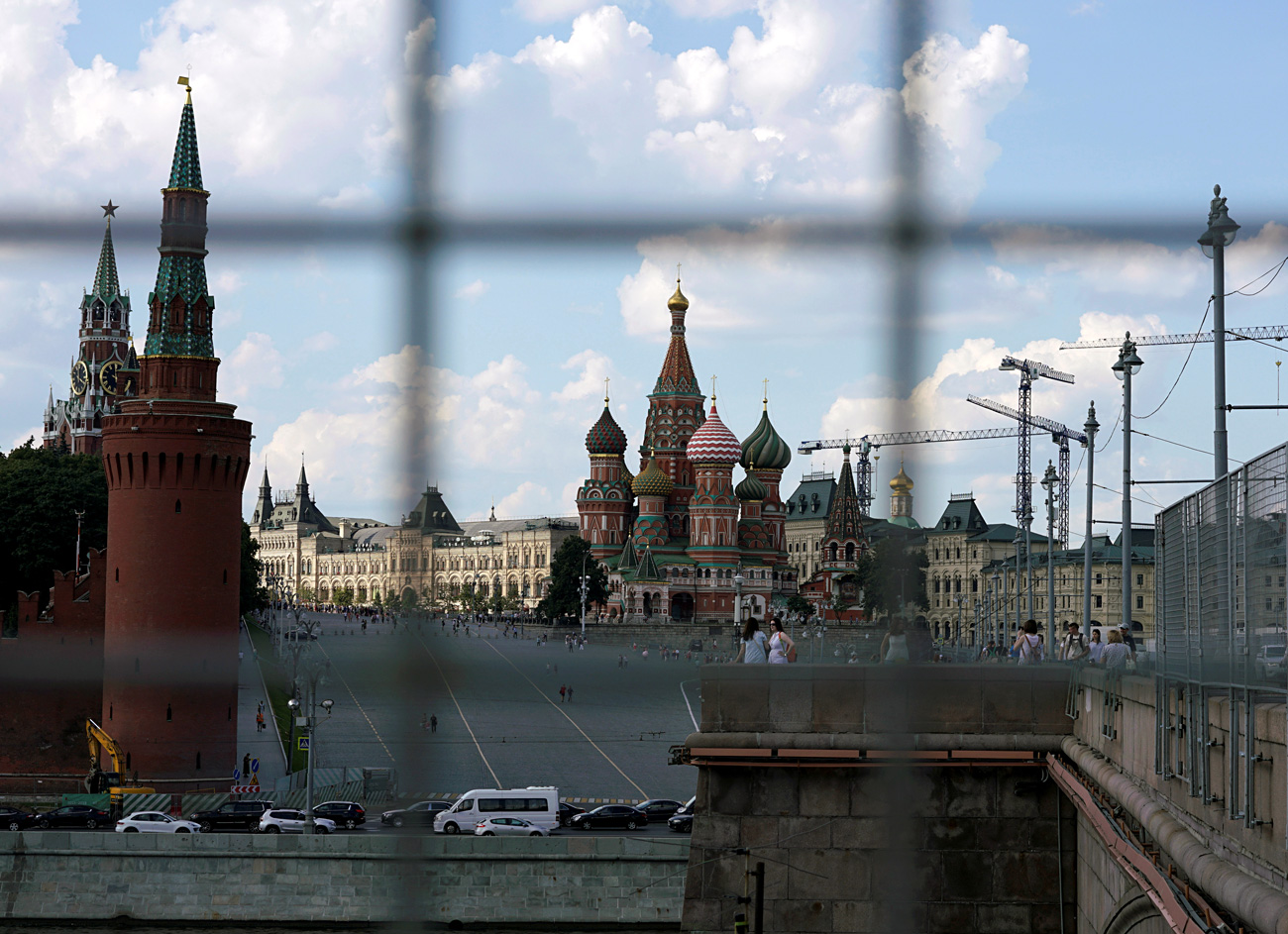 A view through a construction fence shows the Kremlin towers and St. Basil's Cathedral on a hot summer day in central Moscow, Russia, July 1, 2016.