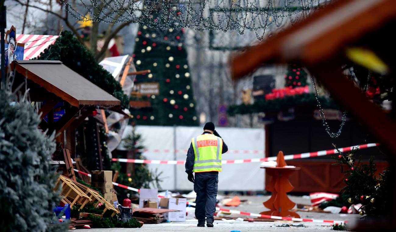 Policist na božičnem sejmu v bližini Kaiser-Wilhelm-Gedaechtniskirche (Spominske cerkve Cesarja Wilhelma), dan po terorističnm napadu v središču Berlina 20. decembra 2016. V napadu s tovornjakom je umrlo 12 ljudi.