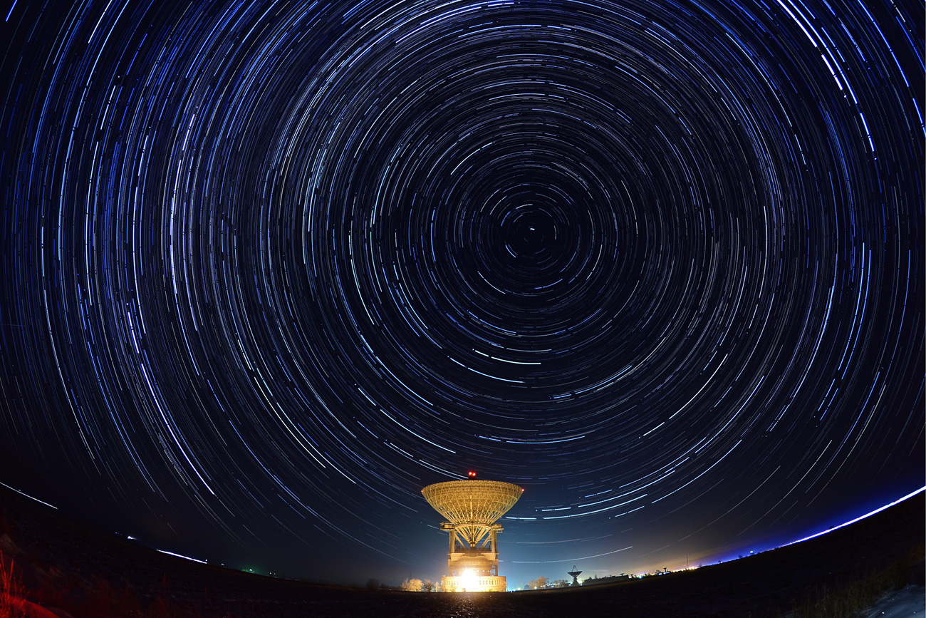 Meteors streak across the night sky over the Galenki RT-70 radio telescope.