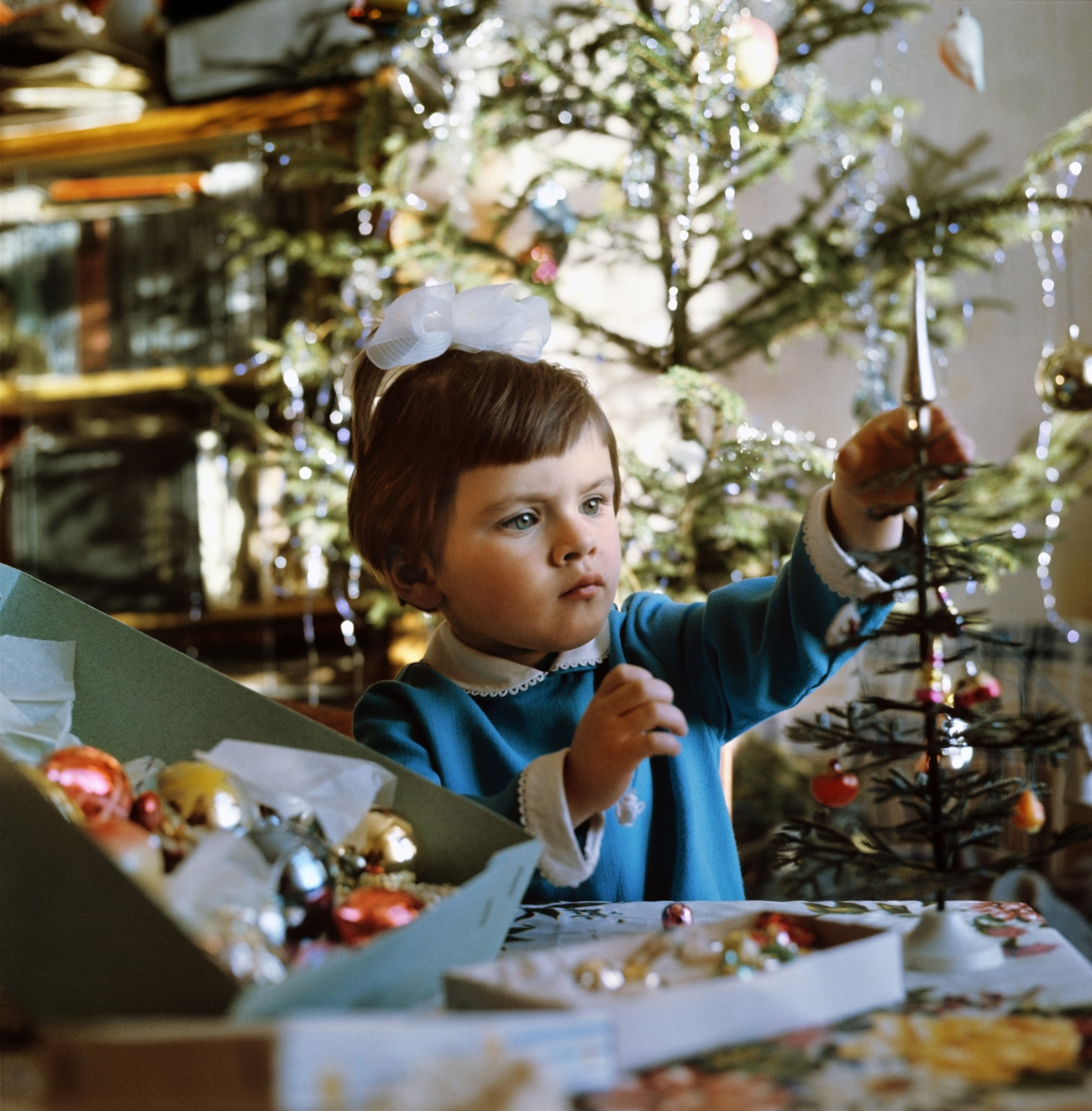 New Year is coming. A girl decorates a Christmas tree. 1973