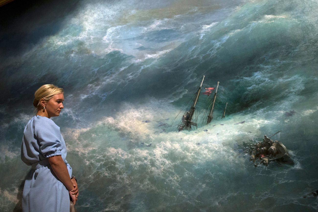 "A woman looks at the ""Wave"" painting by Ivan Aivazovsky, Russian Romantic painter, who is considered one of the greatest marine artists in history, in Tretyakov Picture Gallery on Krymsky Val in Moscow, Russia"