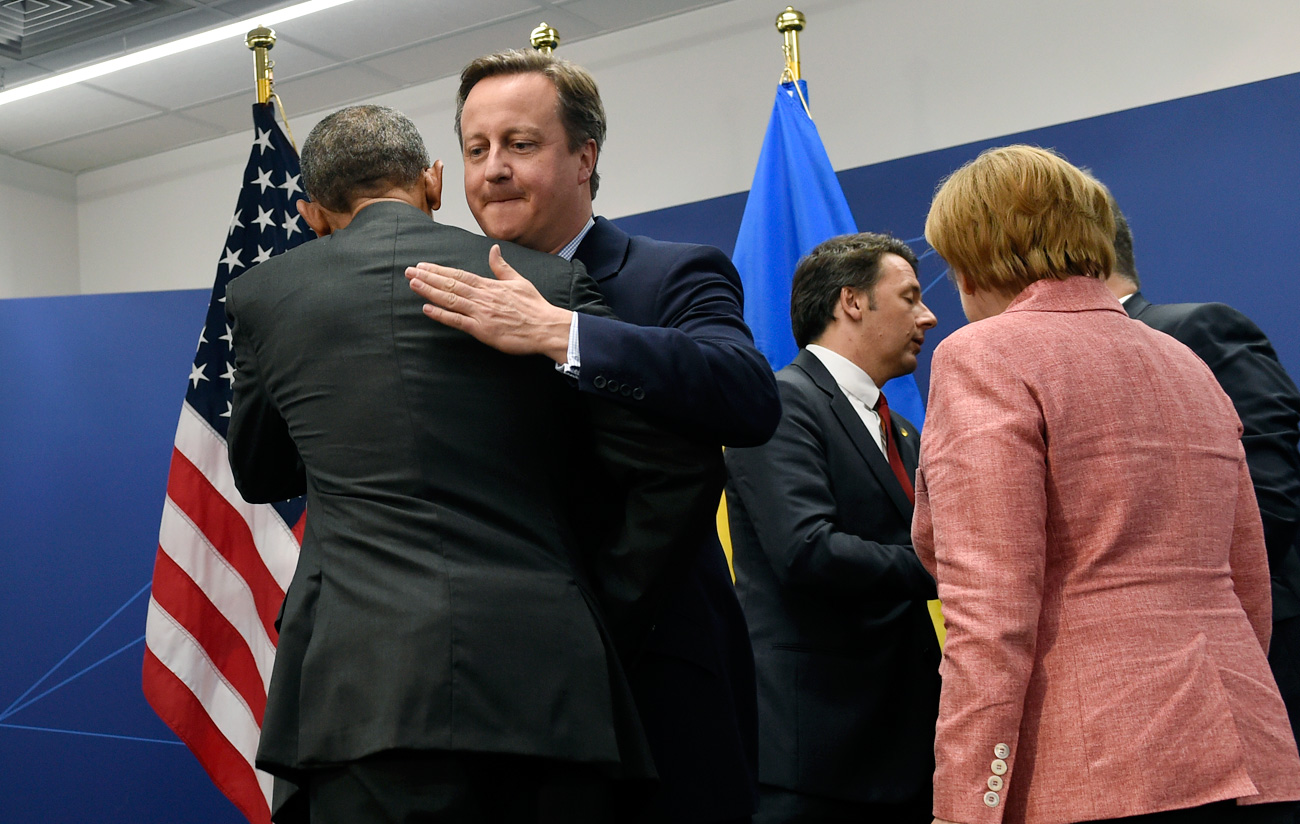 President Barack Obama hugs British Prime Minister David Cameron as Italian Prime Minister Matteo Renzi, second from right, and German Chancellor Angela Merkel, right, talk at PGE National Stadium in Warsaw, Poland, July 9, 2016.