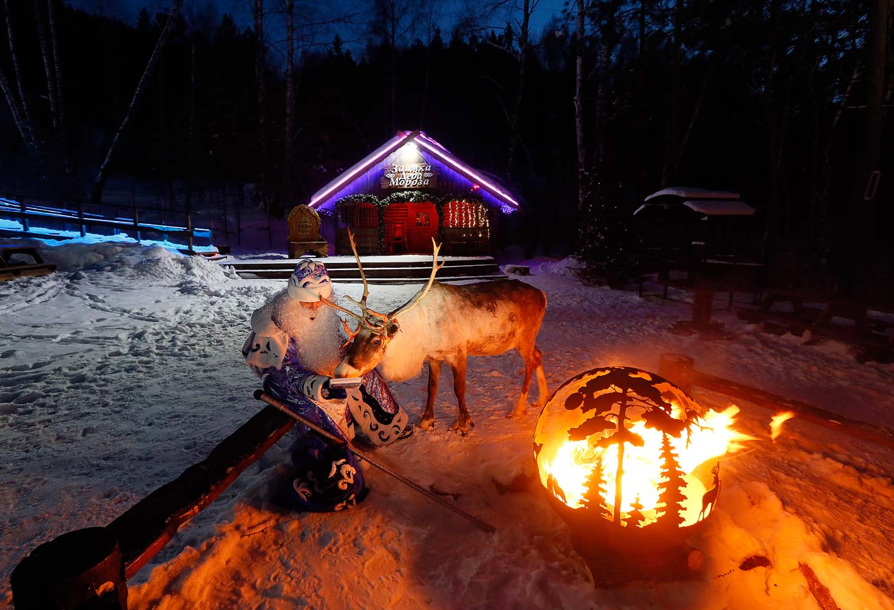 A man dressed as Ded Moroz (Father Frost, Russian equivalent of Santa Claus), sits by the fire with a reindeer Yakut, marking winter solstice at the Royev Ruchey Park of Flora and Fauna in the Siberian Taiga wood in the suburbs of Krasnoyarsk (2,500 miles east from Moscow).