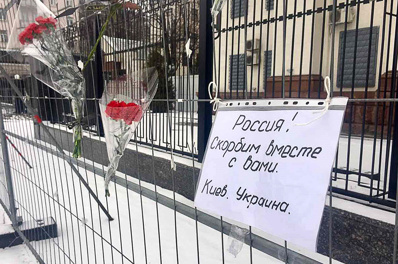 """Flowers near the Russian Embassy in Kiev, Ukraine. The text reads: """"Russia! We are mourning with you. Kiev, Ukraine."""""""