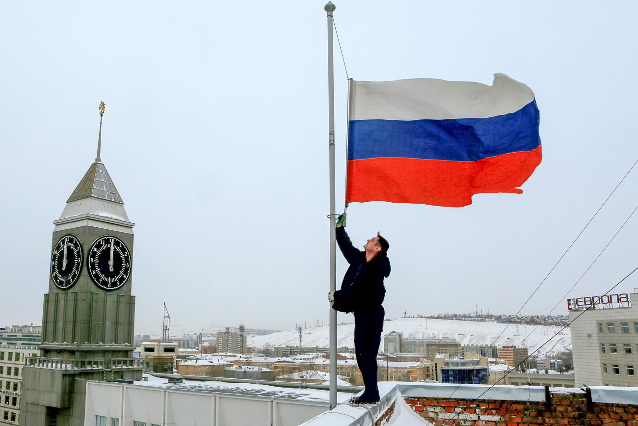 A worker lowers the Russian national flag to half-mast on a roof of the city administration building, as the country observes a day of mourning for victims of the Tu-154 plane which crashed into the Black Sea on its way to Syria on Sunday, in Krasnoyarsk, Russia, December 26, 2016.