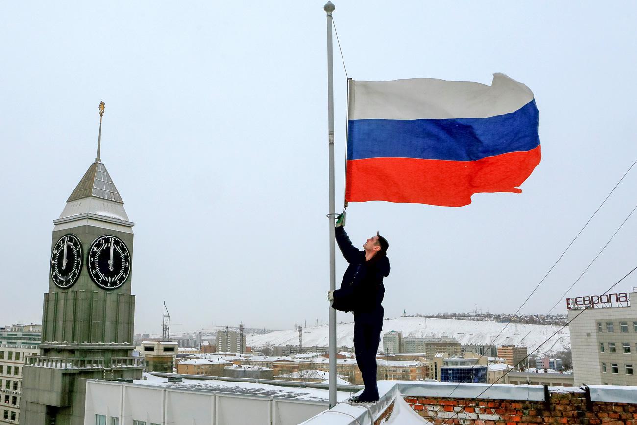 Работник го спушта знамето на Русија на половина копје на зградата на администрацијата по повод Денот на жалоста за загинатите во авионската несреќа на авионот Ту-154. 26 декември 2016, Краснојарск, Русија.