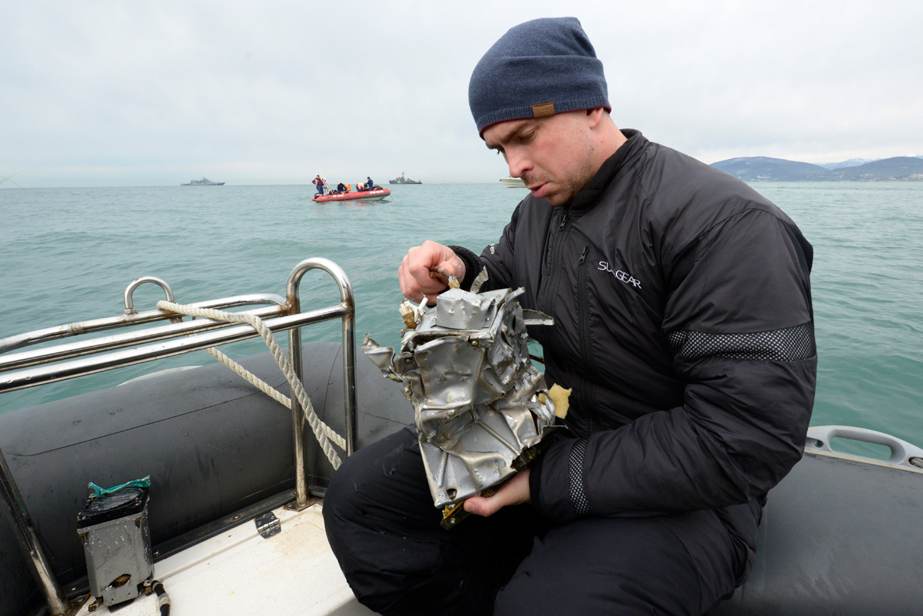 A Russian Emergency Ministry diver inspects a fragment of a plane in the Black Sea, outside Sochi, Russia, Tuesday, Dec. 27, 2016. Investigators have recovered the flight-data recorder from a crashed Russian military plane.