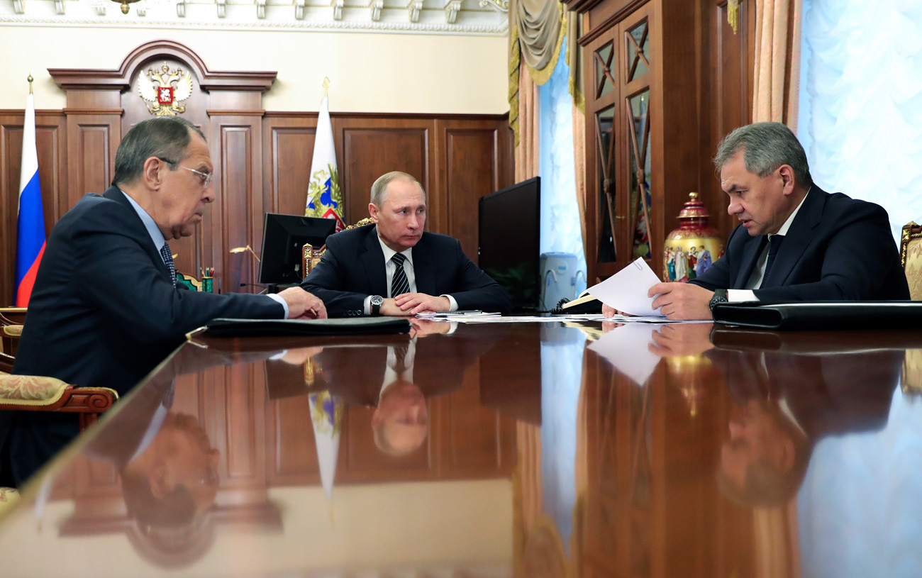 Vladimir Putin and Foreign Minister Sergey Lavrov (L) listen to Defense Minister Sergei Shoigu in Moscow on Dec. 29, 2016.