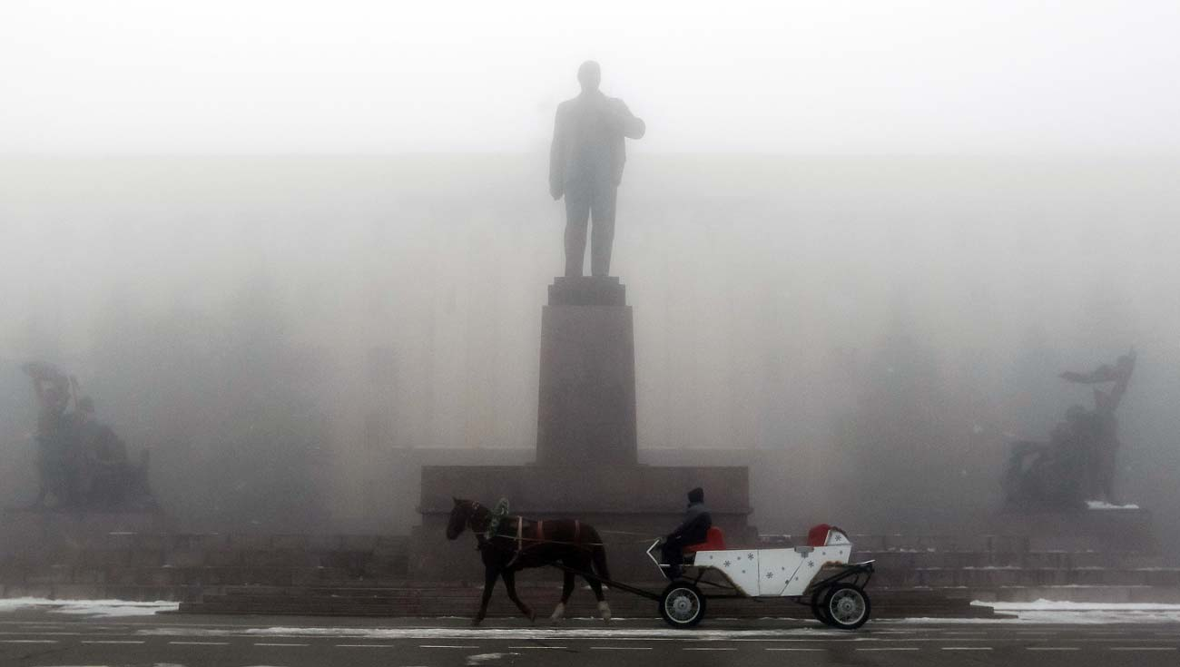 A man rides on a horse cart past a monument of Soviet State founder Vladimir Lenin on a central square during a foggy day in Stavropol, southern Russia