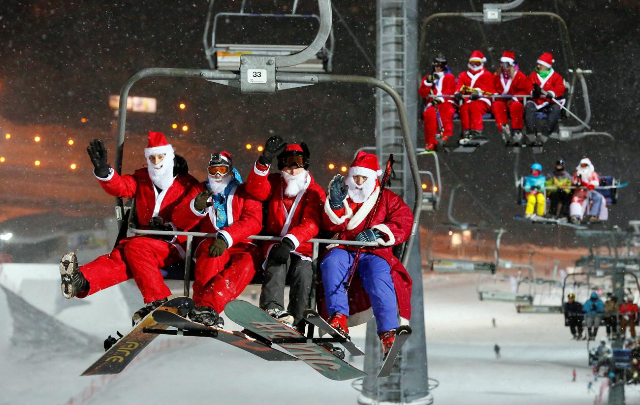 """Скијачи и сноубордери облечени како Дедо Мороз и Снегурочка се возат со лифт за Ноќта на Дедо Мраз и Снегурочка по повод претстојната новогодишна прослава во скијачкиот центар """"Боброви Лог"""" во предградието на Краснојарск, Сибир, Русија."""