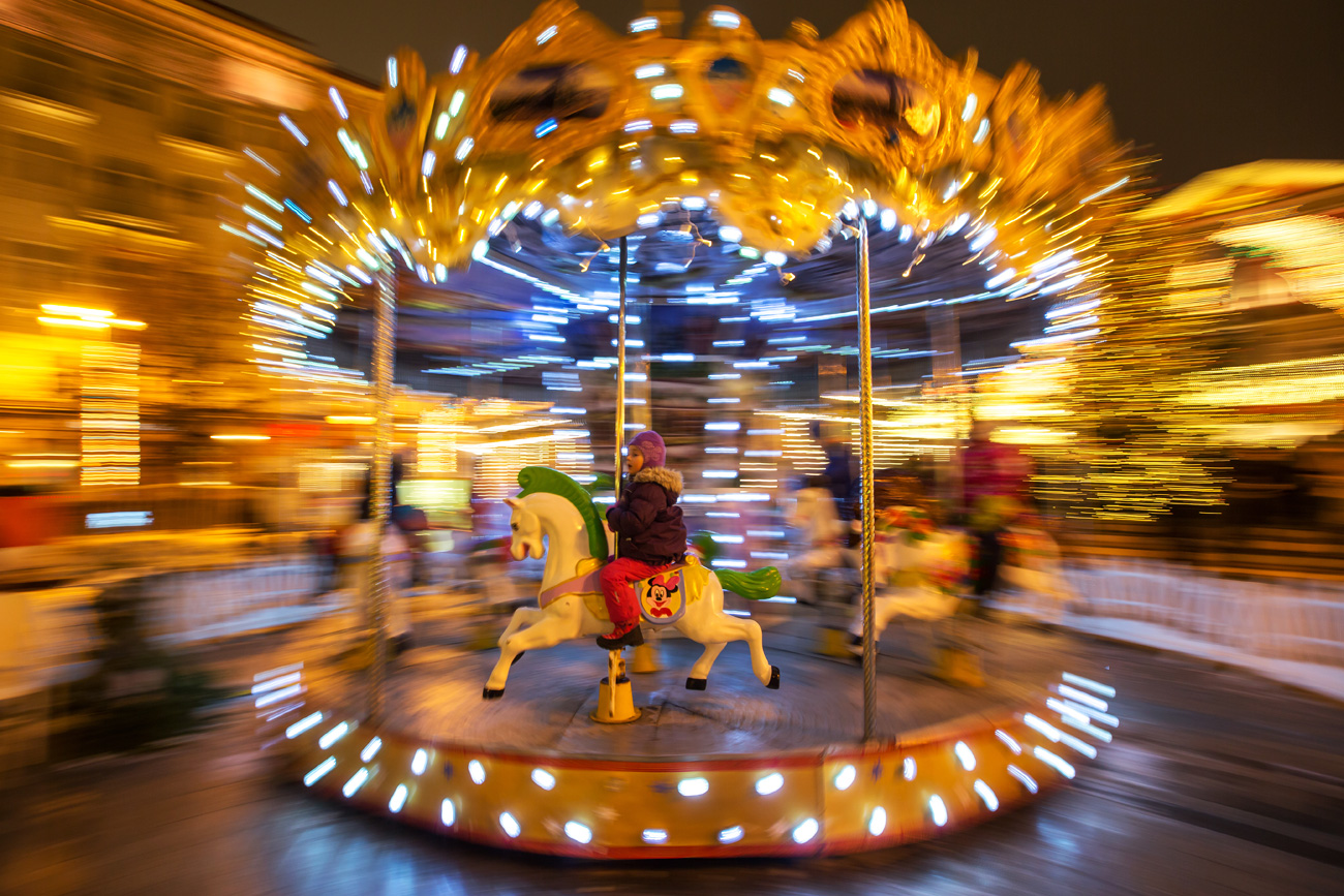 MOSCOW, RUSSIA - DECEMBER 31, 2016: People on a merry-go-round in Tverskaya Street in central Moscow during the Puteshestviye v Rozhdestvo (Journey to Christmas) Festival.