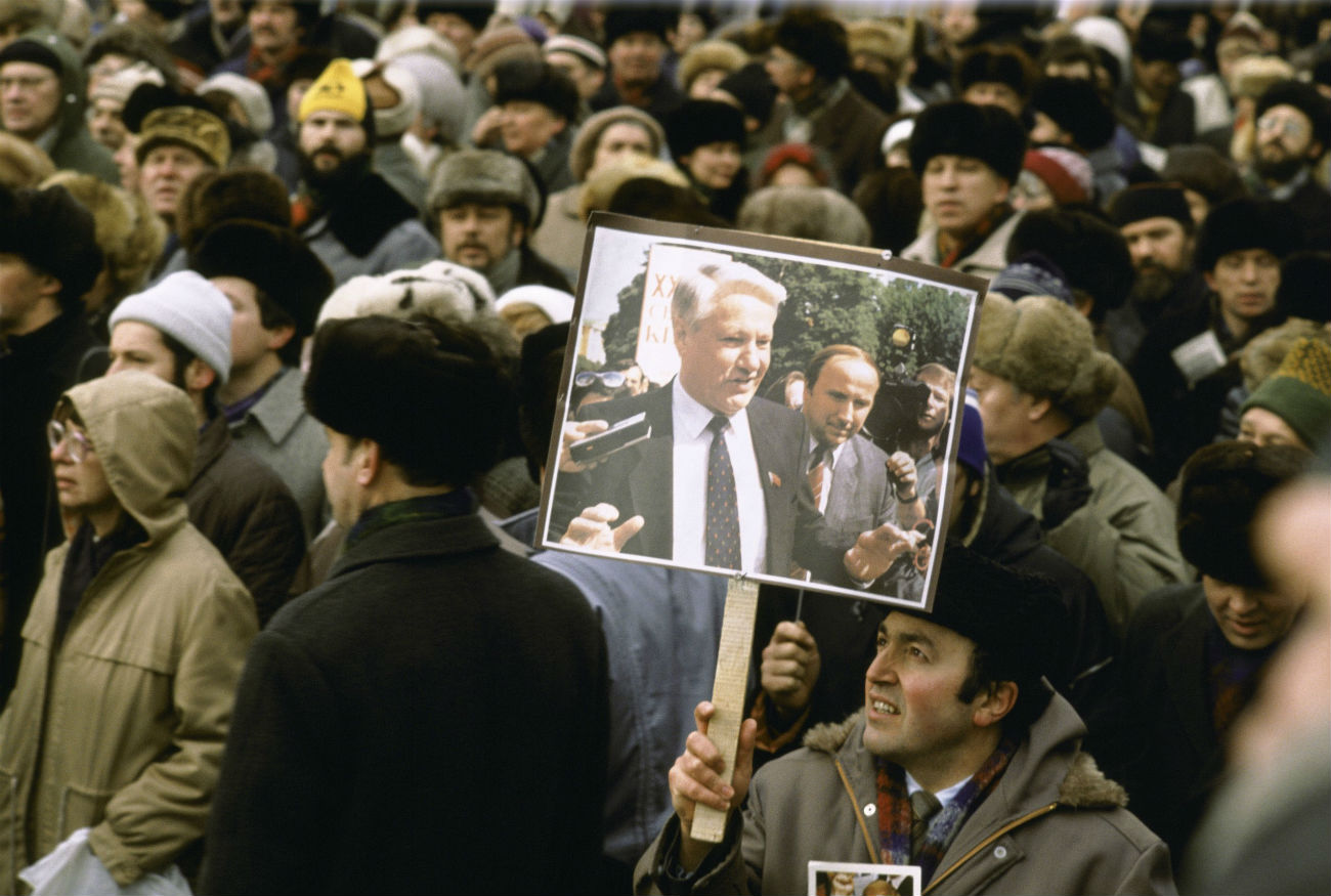 Homem segura cartaz com foto de Iéltsin em uma manifestação pró-democracia em março de 1991, em Moscou
