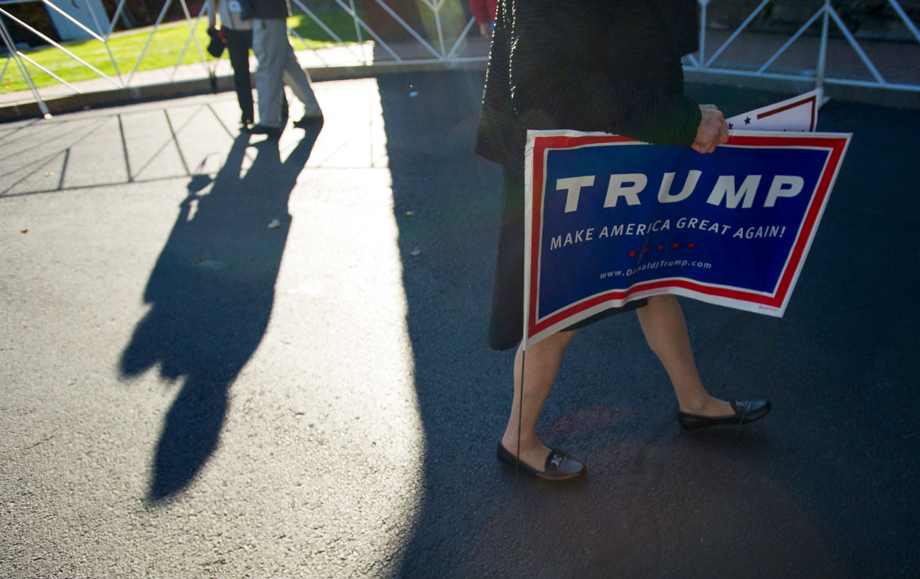 A woman carries a sign for U.S. Republican presidential candidate Donald Trump following a campaign event in Atkinson, New Hampshire, Oct. 26, 2015