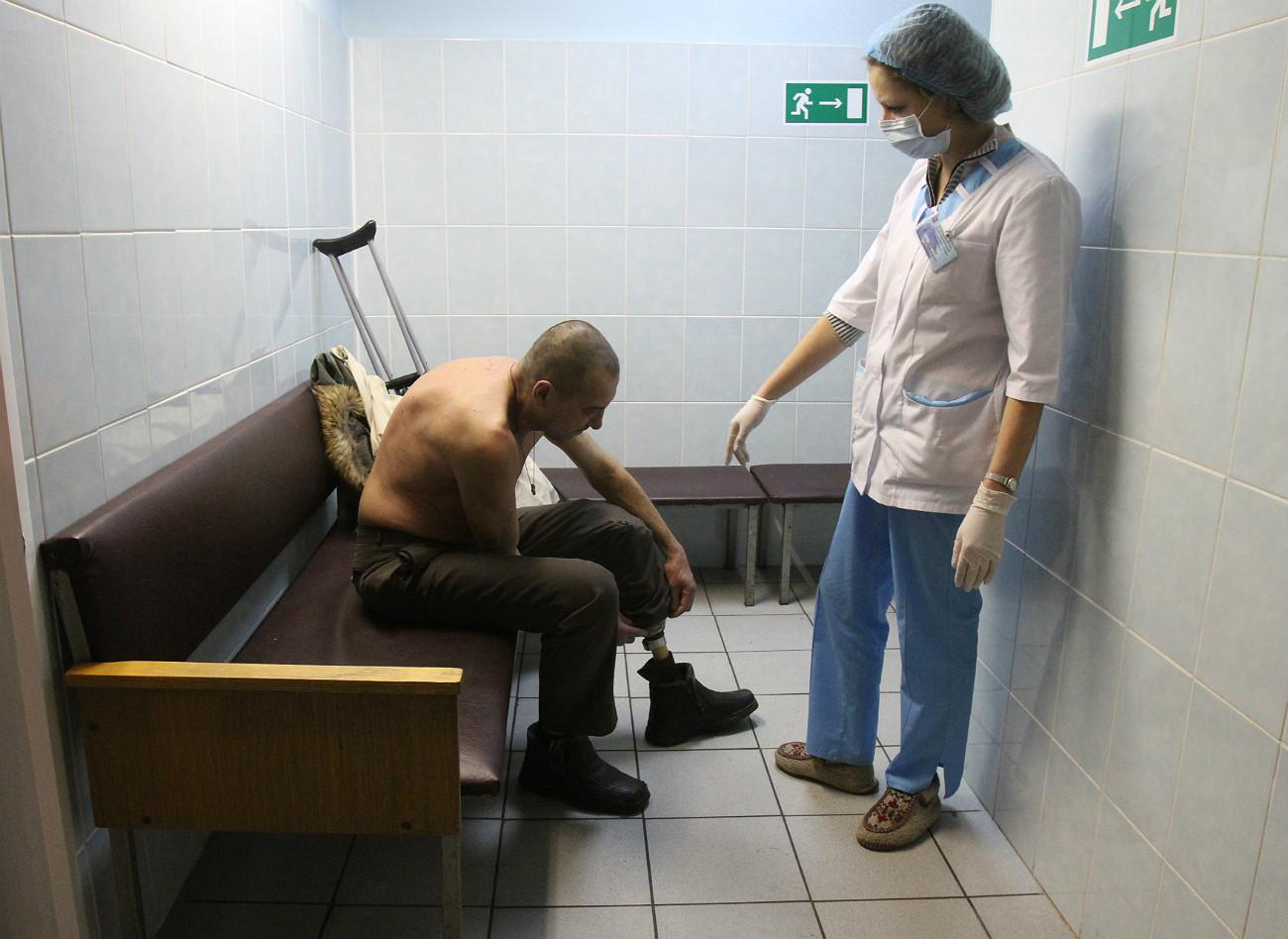 Un'infermiera assiste un clochard in uno dei tanti centri di accoglienza per senzatetto a Mosca. Fonte: Reuters