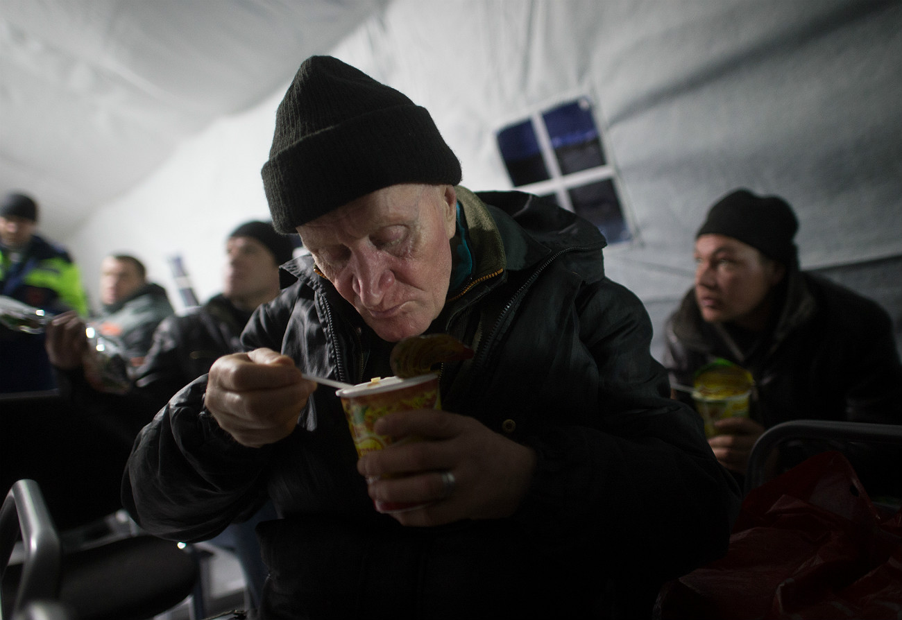 A man has lunch in a heated place for homeless people in the courtyard of the Synodal department for church charity and social services on Nikoloyamsky street in Moscow.