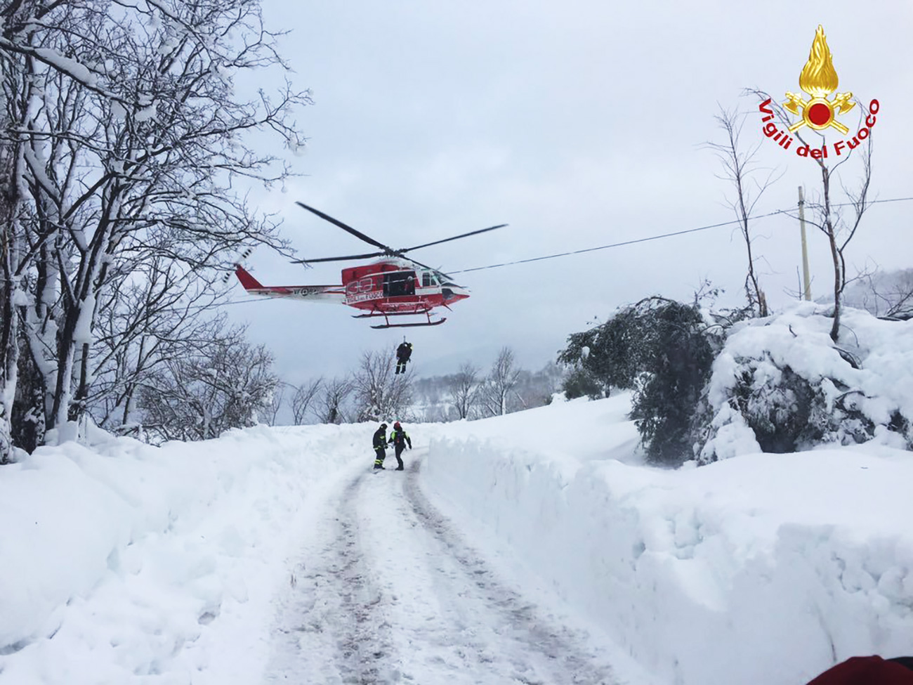 Firefighters and a helicopter during rescue operations near the hotel 'Rigopiano', which was buried in an avalanche, in the region of Abruzzo near Farindola, Italy, Jan. 19, 2017. A avalanche caused by an earthquake buried the hotel.
