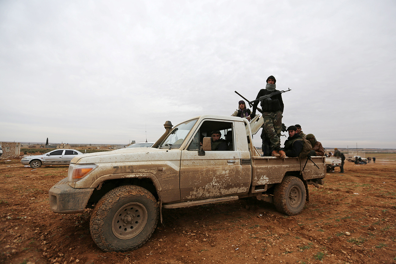 Rebel fighters ride a pick-up truck on the outskirts of the northern Syrian town of al-Bab, Syria Jan. 14, 2017.