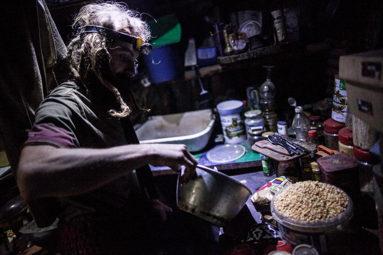 O eremita prepara sua comida em uma cozinha feita por ele mesmo. Mas, para poder enxergar ali, ele precisa usar duas lanternas: uma na testa, e outra pendurada no teto.