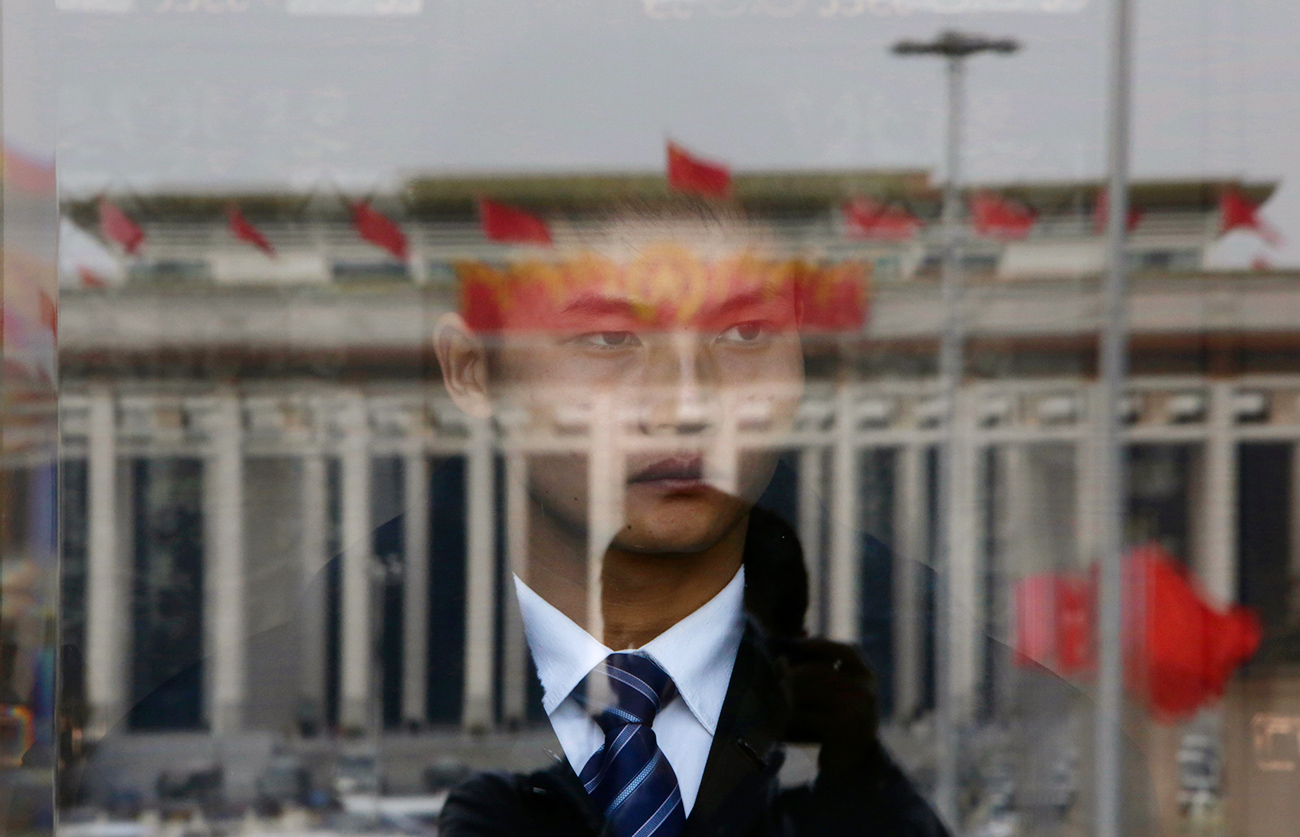 A soldier in plain clothes from the Chinese People's Liberation Army (PLA) stands guard behind an entrance of the Great Hall of the People, the venue of the annual session of China's parliament, as red flags are reflected on a glass door in Beijing