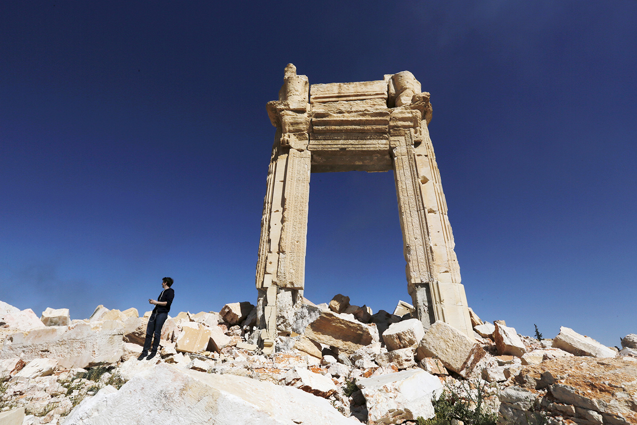 A journalist stands at the remains of the Temple of Bel in the historic city of Palmyra, in Homs Governorate, Syria.